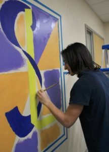 Southern Local High School senior Jesse Harris adds a little color to the walls of a conference room in the school, which will display an original mural. (Submitted photo)