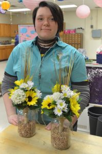 Aubrey Albright, a Carrollton student attending Buckeye Career Center, displays an arrangements created in the floral department at the career center.