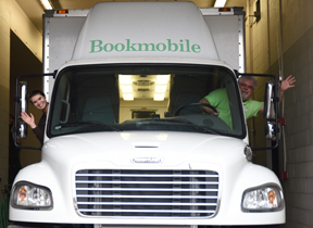 Lauren McNutt (left) and David Garrett head out to several stops around the county in the Carroll County District Library Bookmobile. They will be waving in honor of National Bookmobile Day April 12.