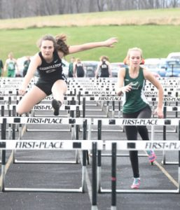 Carrollton hurdler Mac Tubaugh clears a hurdle ahead of a West Branch competitor during a meet last week at Carrollton. Tubaugh finished third in the event.