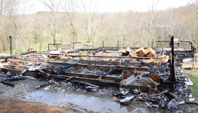 Poles from the porch structure and the cement block base were the only remaining pieces of a double-wide home that was destroyed by fire in the early morning hours of April 19. Coroner Dr. Mandal Haas is awaiting identification of a body discovered in the rubble.