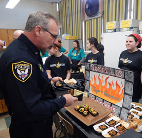 Carrollton Police Chief Bob Ellington (left) views information provided by the winning team in the Warrior Test Kitchen Challenge at Carrollton Schools recently. Three of the four winning team members are shown in the background.