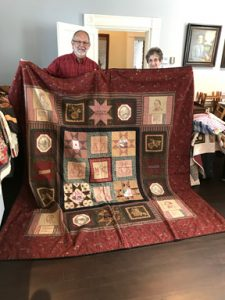 Dave Lewis (left) and Charlene Good hold a McCook Family themed quilt which will be on display in the McCook House through July.