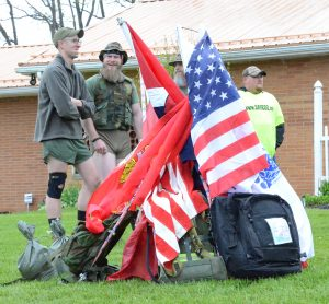 Members of 22 2 None from Michigan wait with their backpacks and flags for step off of the SAVE22 hike Saturday. They are (from left): Ben Gunderson, Dave Winkle, Ray McDaniel (between the flags) and a security man.
