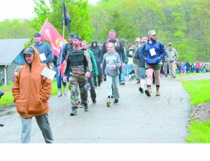 Walkers head toward Brenner Rd., beginning the seven-mile hike to bring awareness to veteran suicide Saturday morning.