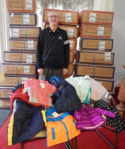 Tom Turnipseed stands in front of cases of coats from Operation Warm in Indiana. Each case contains six coats in specific sizes and gender. An assortment of new coats Carroll County Coats for Kids has received this year are displayed on the chairs. (FPS/Leigh Ann Rutledge)