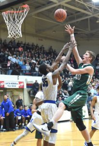 Malvern forward Mark Mayle lifts a shot over the outstretched arms of Luthern East center Justin Motley during the regional game.