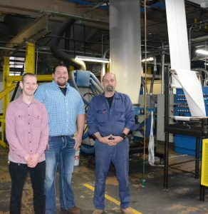 Nathan Shuman (left), a shift supervisor; Michael Keaton (center), production manager; and Ed Serri, maintenance manager, are shown inside the manufacturing facility. A machine that produces the blown film bags is shown operating in the background.