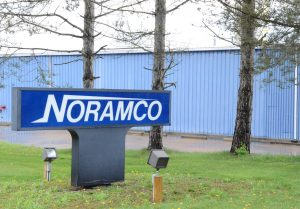 The plastic trash bag company known as Noramco sits quietly on a back street in Carrollton; the blue factory mostly hidden by a row of pine trees.  A sign at the street designates the name of the facility.